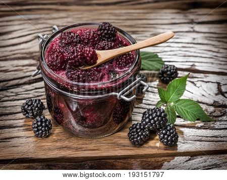 Blackberry confiture on old wooden table. Several fresh berries are near it.