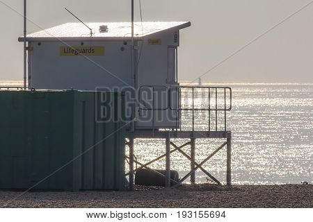 Lifeguard lookout station overlooking calm sea on a sunny hazy morning. Seaside safety and drowning prevention. Beach health and safety building for swimmers.