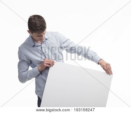 Young pry man portrait of a confident businessman showing presentation, pointing paper placard gray background. Ideal for banners, registration forms, presentation, landings, presenting concept.