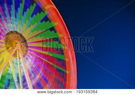 Ferris wheel on blue sky copy space. Long exposure
