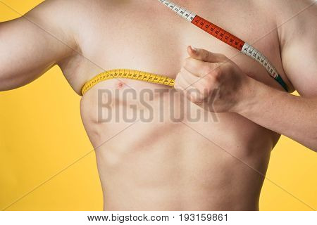 Diet, slimming, sports, athlete on a yellow background.