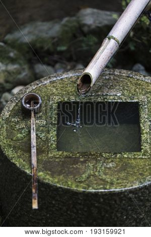 Japanese style traditional bamboo fountain and stone basin for hand washing at Ryoan-ji Temple Kyoto Japan