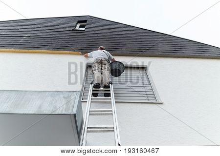 plasterer staying on ladder and covering the roof underside with a layer of render