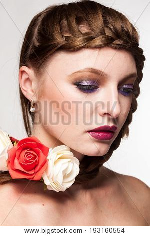 Woman with flowers arround her in studio photo. Beauty and fashion. Glamour and summer