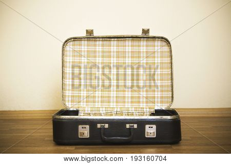 Open old black leather suitcase in retro stile. Suitcase for trip and travel. Black open suitcase on the floor. Checkered suitcase on the floor. The wait before the trip. Vintage accessories for business. Travel bag for summer vacation to travel by train.