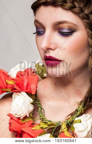 Portrait of beautiful woman with flowers arround her neck in studio photo. Beauty and fashion. Glamour and summer