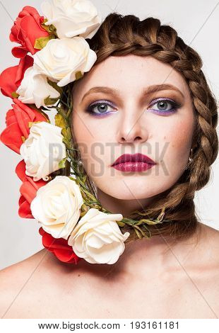 Beautiful Woman with flowers arround her head in studio photo. Beauty and fashion. Glamour and summer
