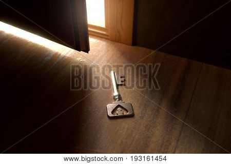 3d rendering of rusty vintage key laying on wooden floor in front of lighten open door