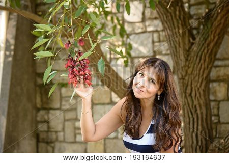 A nice girl posing under a tree touching red flowers and smiling