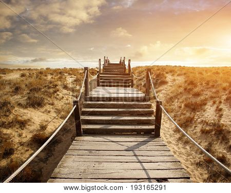 Wooden walkway over the sand dunes to the beach at sunset