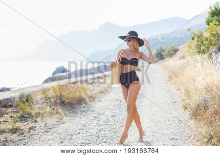Young beautiful woman with a slender figure, blonde in dark sun glasses and a big black hat from the sun, black bikini, beach bag beige, posing alone outdoors in the summer against the backdrop of mountains, rocky beach and ocean