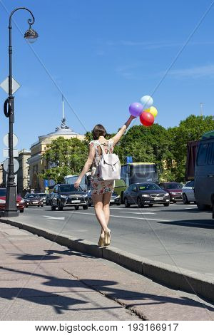 slender girl with a beautiful figure walking down the street along with expensive multi-colored balloons in his hands back backpack