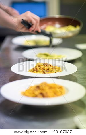 Chef Serving Or Plating Up Pasta In A Restaurant
