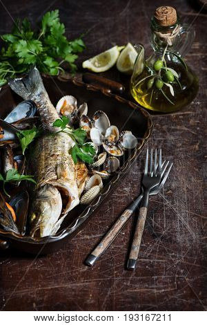 Variety mussels and oven baked seabass with lemon olive oil on old wooden table.