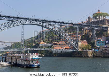 PORTO, PORTUGAL - APRIL 17, 2017: Big boat at the Ribeira in the Douro River bank near the Dom Luis I Bridge, Porto, Portugal.