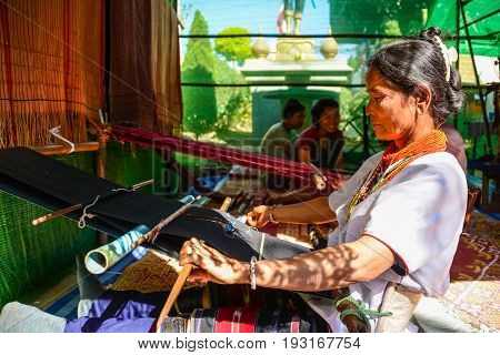 CHIANGMAI THAILAND - JANUARY 24 2015: Indigenous woman is demonstrating weaving fabric in 22nd Traditional Skirt Fabric and The Indigenous Product and Culture Festival in Mae Chaem of Chiangmai Thailand