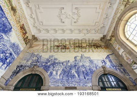PORTO PORTUGAL - JUNE 24 2017: Ancient vintage Azulejos panel on inside walls of main hall of Sao Bento Railway Station in Porto city. Tiles Installed between 1905 and 1906 by artist Jorge Colaco. The building station is a popular tourist attraction.