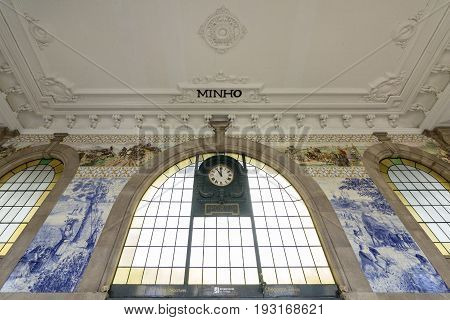 PORTO PORTUGAL - JUNE 24 2017: Ancient vintage Azulejos panel and inside detail of main hall of Sao Bento Railway Station in Porto city. Tiles Installed between 1905 and 1906 by artist Jorge Colaco. The building station is a popular tourist attraction.