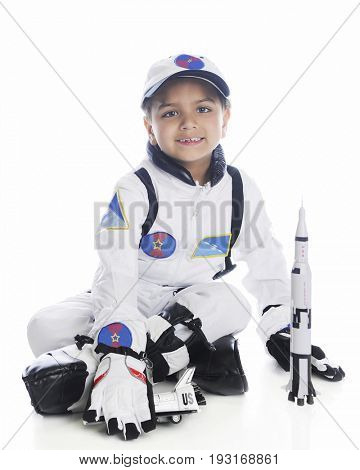 A young elementary boy playing astronaut. He's in his space suit by a toy rocket.  On a white background.