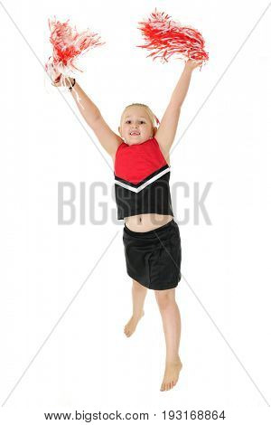 An elementary cheerleader, barefoot but in uniform, jumping high as she practices a cheer.  On a white background.