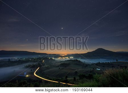 Landscape misty view. Fantastic dreamy sunrise on the mountains with a beautiful starry night. Foggy clouds above the landscape.