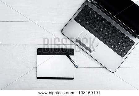 Wooden white office desk table with open blank laptop computer and graphic tablet free space. Top view with copy space. Grey laptop with graphic tablet on wooden table background