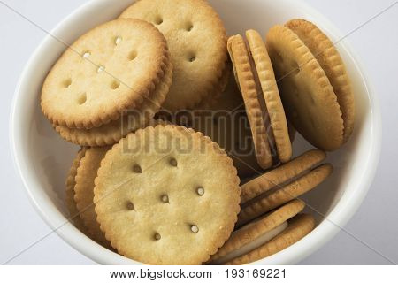 A lot of crackers in a white bowl on the white background