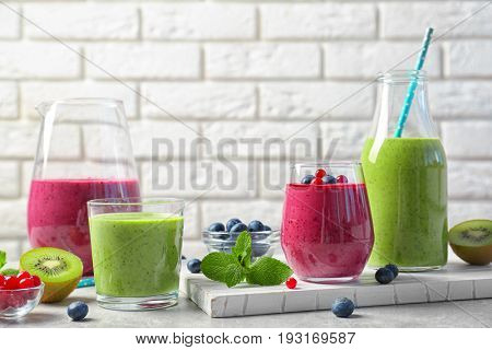 Glassware of fresh yogurt smoothie with berries and kiwi on light table