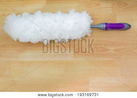 Soft fluffy white furry feather static duster with purple handle on wooden background with copyspace