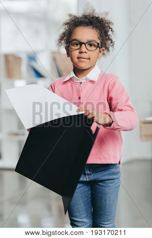 Beautiful Little Girl In Eyeglasses Holding Clipboard With Papers And Looking At Camera