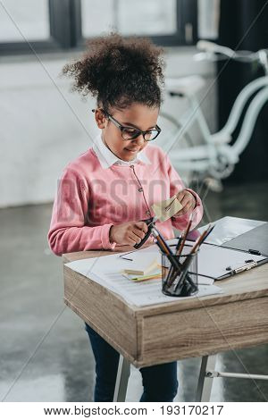 Cute Little Girl In Eyeglasses Holding Scissors And Cutting Paper At Office Table