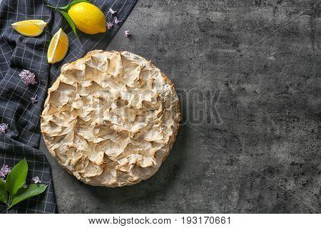 Composition with tasty lemon meringue pie on dark table
