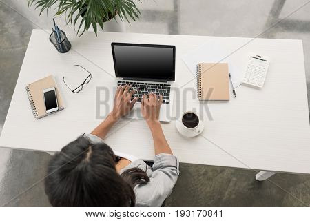 Overhead View Of Businesswoman Using Laptop While Sitting At Workplace In Office