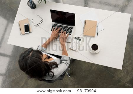 Overhead View Of Businesswoman Typing On Laptop While Sitting At Workplace In Office