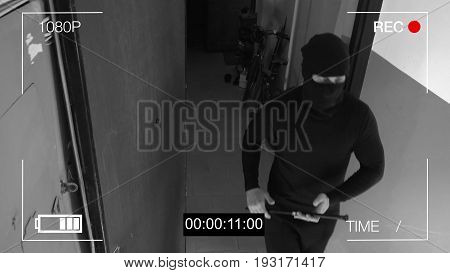 surveillance camera caught the robber in a mask with a crowbar.