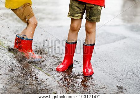 Two children wearing red rain boots jumping into a puddle. Close up. Kids having fun with splashing with water.