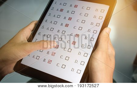 student testing in online exam in form exercise exams answer on tablet with multiple-choice quiz or questions by finger clicking