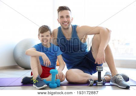 Dad and son sitting on floor with dumbbells in gym