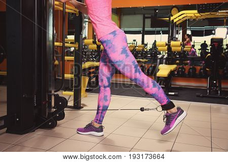 Sporty young woman training legs in gym