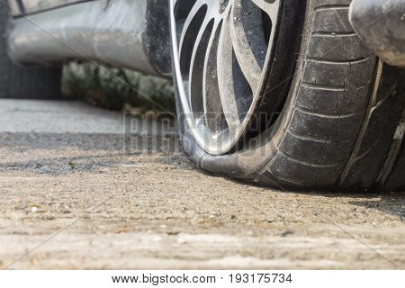 Car flat tire on road, in down town