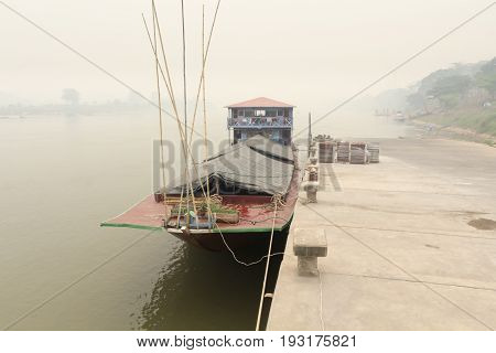 Heavily polluted air from forest fire cover Mekong river at chiang khong port.