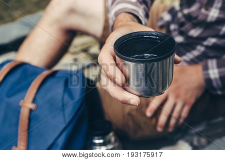 Unrecognizable hiker man drink tea or coffee from thermos closeup. Hiking and leisure theme