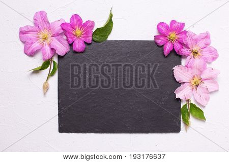 Violet summer clematis flowers and empty slate board on grey textured background. Place for text. Flat lay. Mock up.