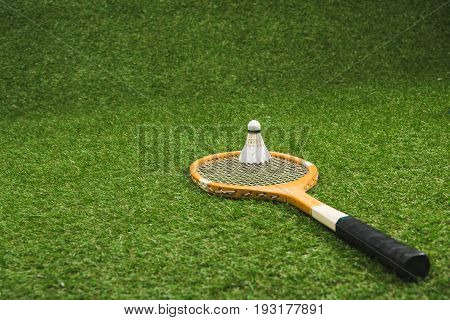 Wooden Badminton Racket And Shuttlecock Lying On Green Lawn