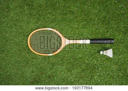 Top View Of Badminton Racket And Shuttlecock On Green Lawn