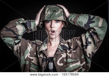 Beautiful shocked female soldier in camouflage