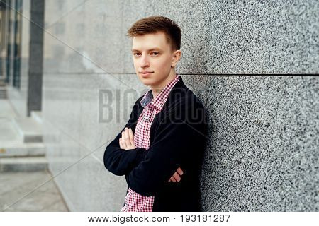 Handsome casual young man in plaid shirt and jacket posing near stone wall outdoors, free space. Teenager with crossed hands. Full body length portrait, fashion and people concept