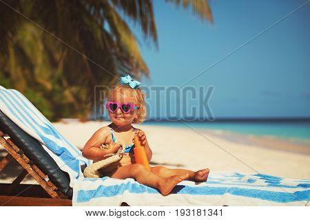 sun protection - cute little girl with sunblock cream on beach