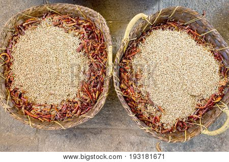 Two wicker baskets with great amount of fried whole coriander seeds and chili peppers. Preparation for the feast in a Hindu temple