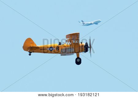 Wantagh N.Y USA - 26 My 2017: Yellow world war II Biplane flying during practice for the airshow over Memorial Day weekend at Jones Beach State Park with a commercial flight in the background.
